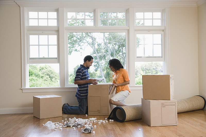 couple unpacking boxes at new house_small