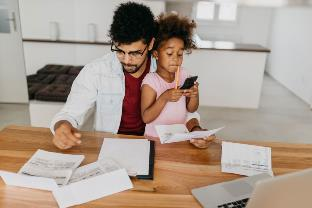 dad and daughter paying bills without automation
