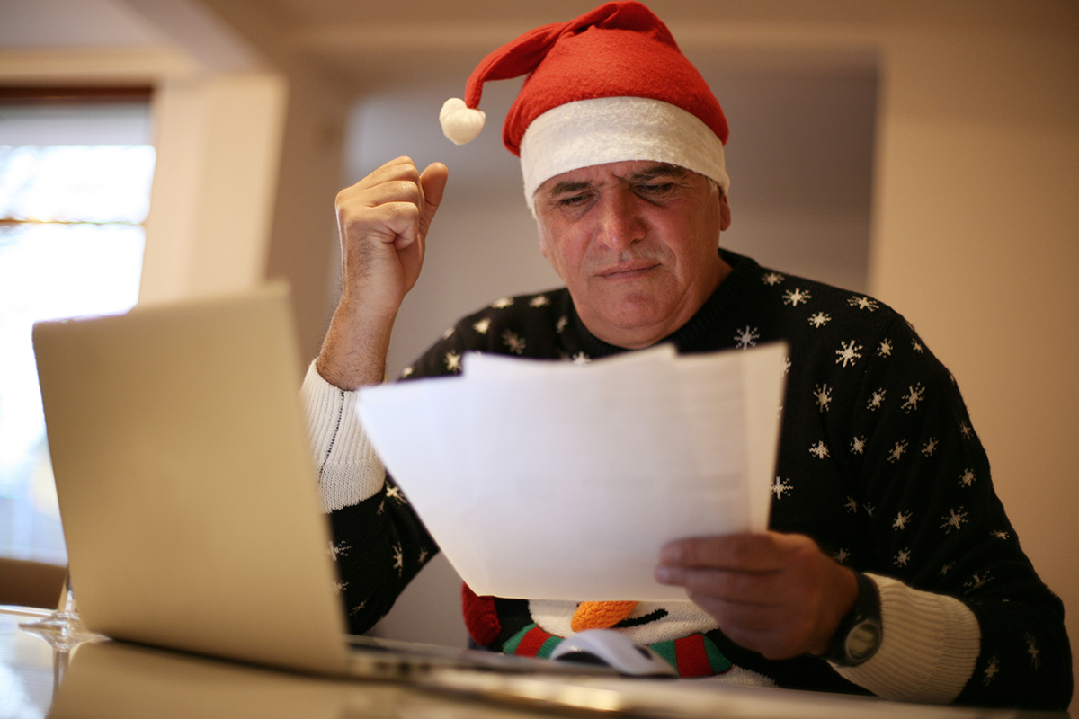 senior man working on budget in santa hat