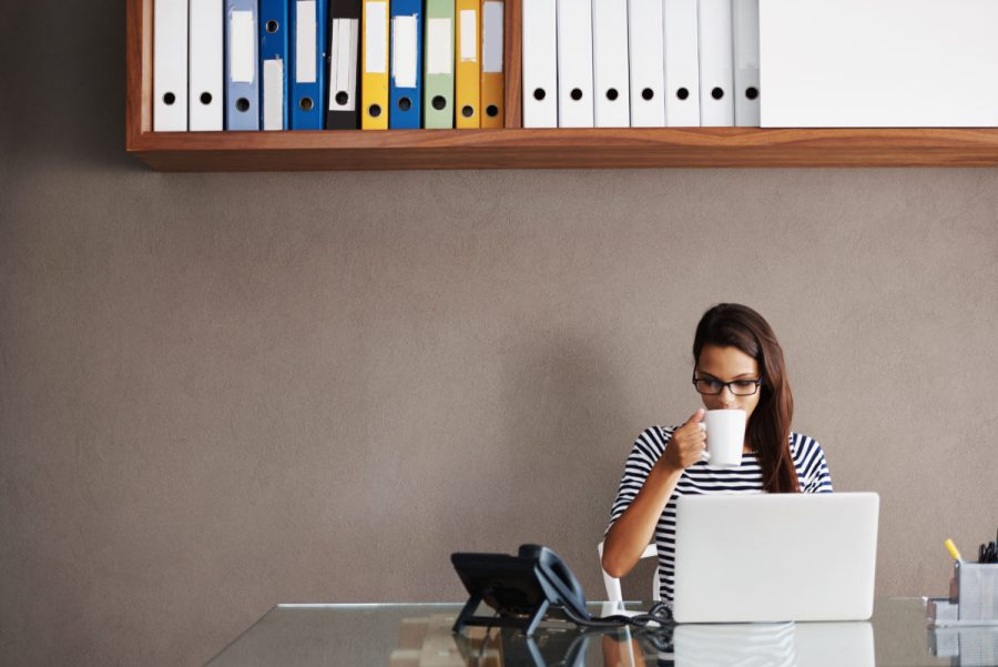 woman-sipping-coffee-at-her-desk