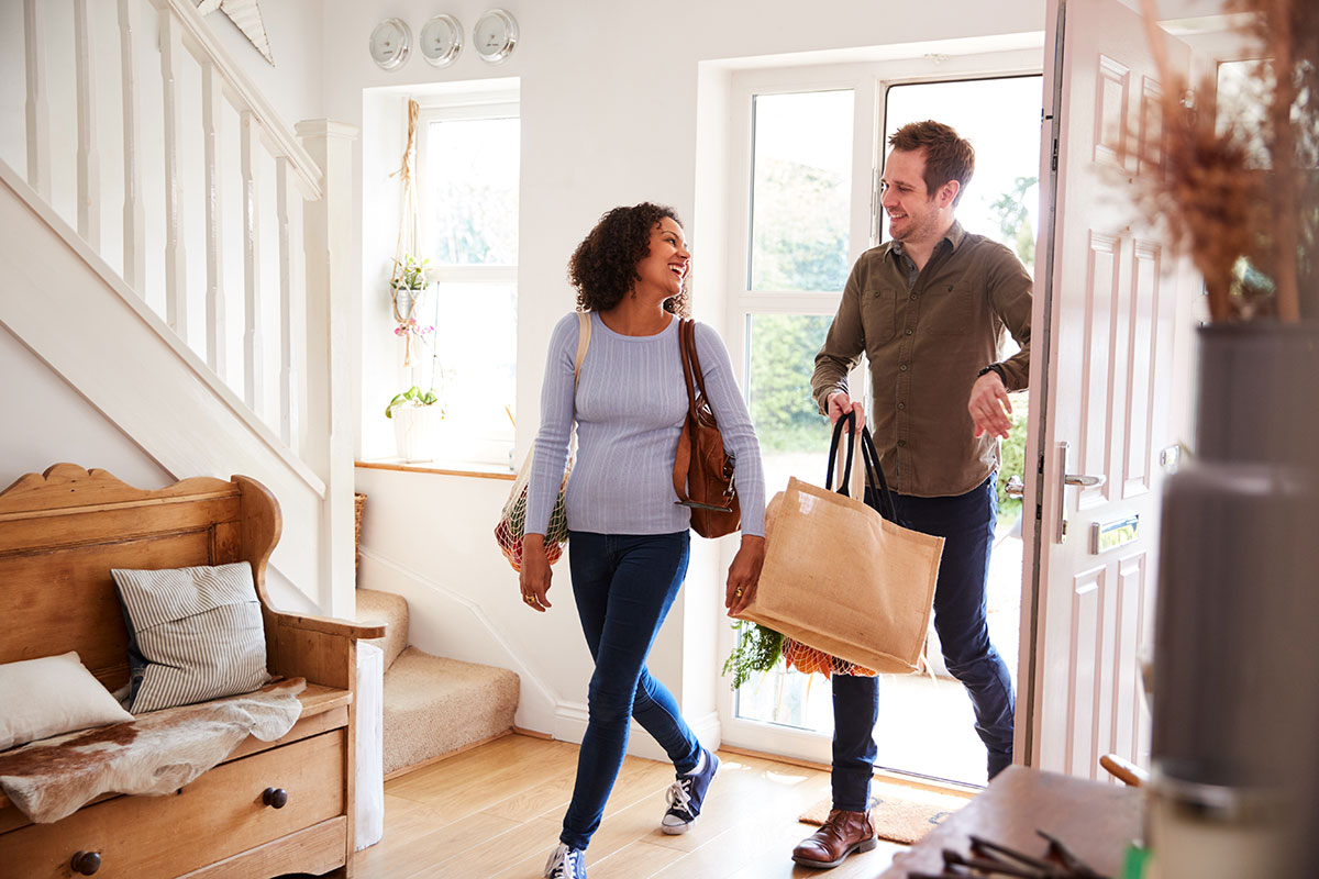 Couple walking into home with groceries
