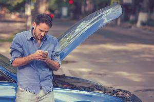 Man on phone with broken down car