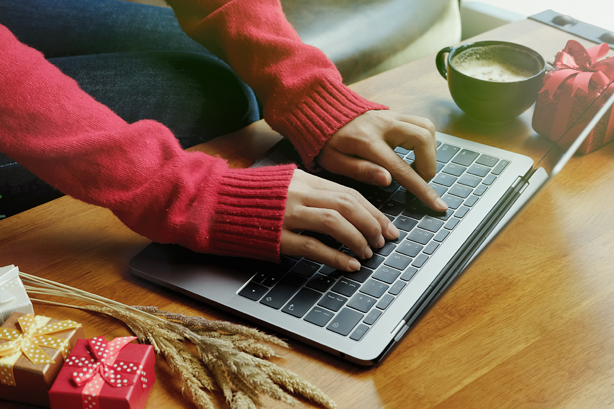 Woman typing on computer for holiday shopping