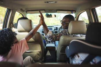 Dad and daughter clapping in the car
