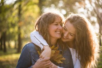 Aging mother and daughter smiling