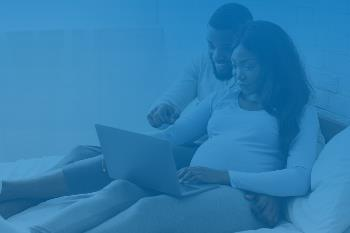 Pregnant woman and partner looking at computer