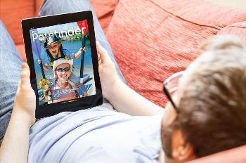 Guy laying on couching reading magazine on tablet