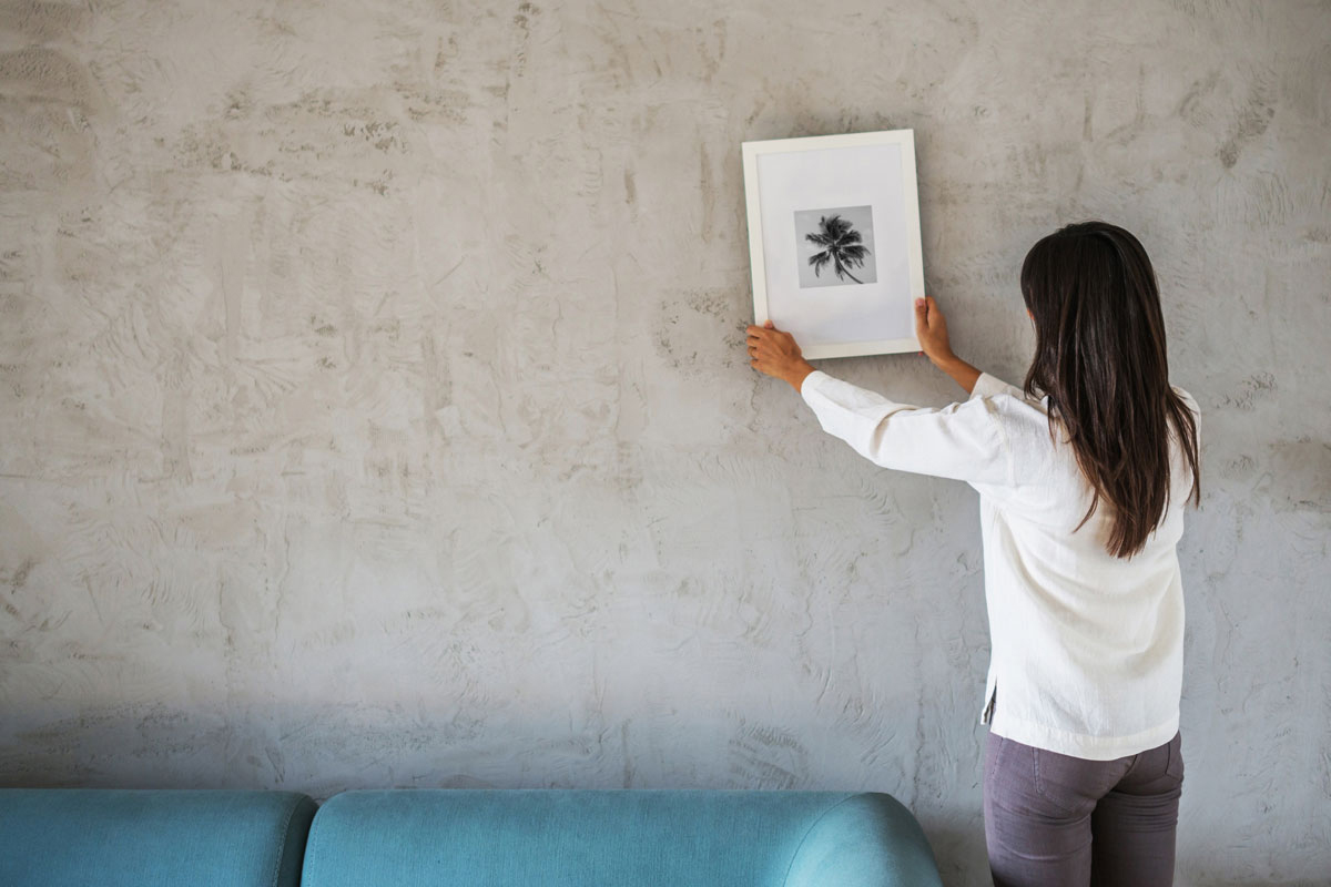 Woman hanging picture