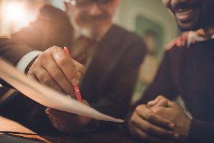 men signing documents