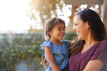 Hispanic mom and young daughter laughing