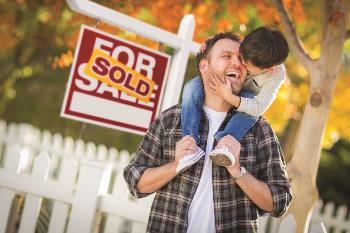 Father and son in front of a house sold sign