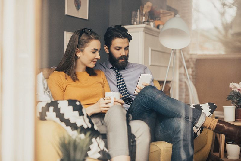 millennial couple reading money articles on phone