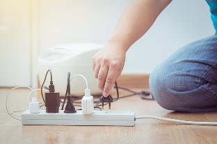 man plugging in to power strip