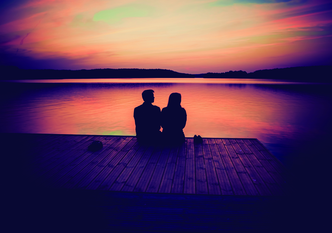 Man and women sitting on a dock looking out onto a sunset