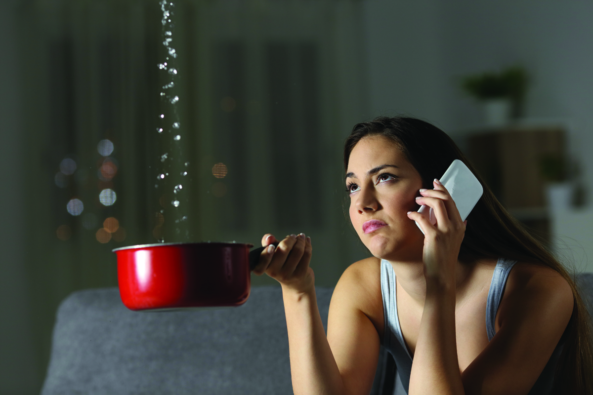Women on the phone holding a pan that water is dripping into from her ceiling