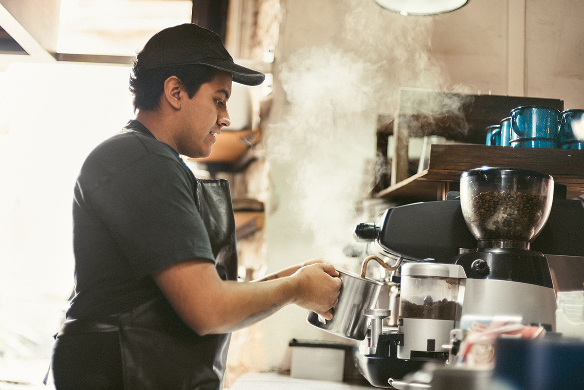 young man working second job as a barista