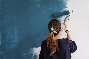young woman painting wall blue
